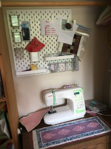 sewing machine with peg board above it and small purple table runner quilt on the desk