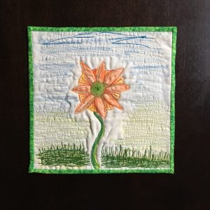 small art quilt of orange flower, with the binding now stitched on, all finished because I created a strong why